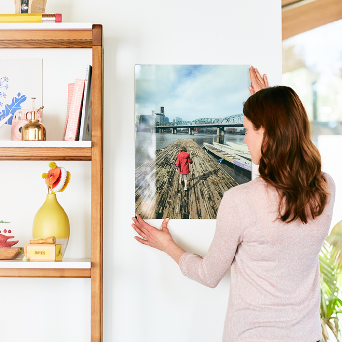 women hanging a glass print on a wall