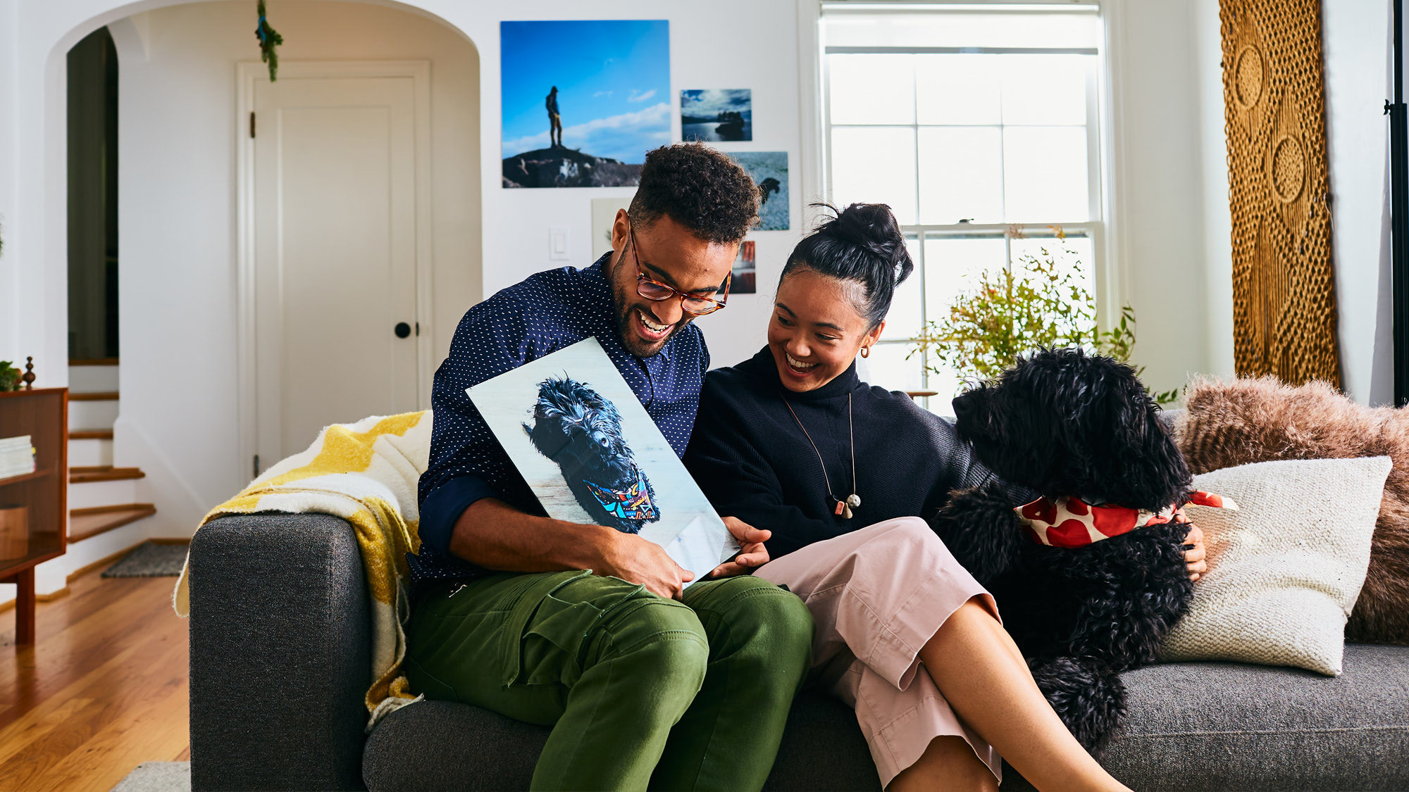 Couple looking at Fracture print of dog while sitting on couch
