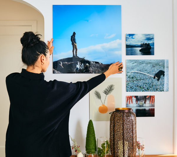 Woman hanging photo wall with five Fracture glass prints
